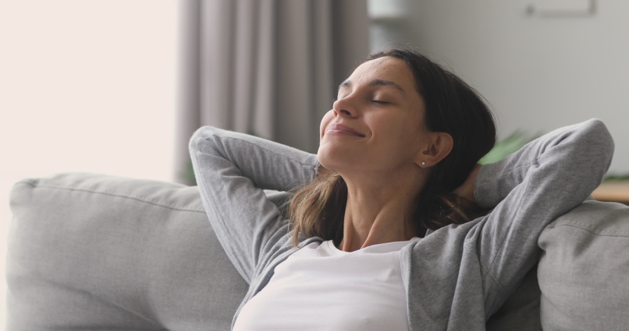 Happy relaxed young woman rest lounge lean on couch enjoy peaceful mood, healthy lazy calm girl dreaming breathing fresh air sit on comfortable sofa in living room on stress free cozy day at home | Shutterstock HD Video #1032911126