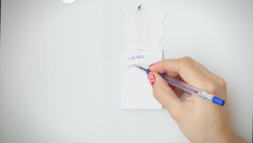 Woman inspecting refrigerator shelves indoors and she marks Check list note on a fridge door with magnet