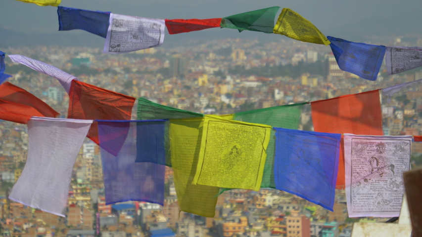 SLOW MOTION, CLOSE UP, DOF: Multicolored prayer flags flutter over city of Kathmandu in the back. Beautiful shot of buddhist flags suspended from a Swayambhunath stupa moving in the autumn breeze. | Shutterstock HD Video #1032944276