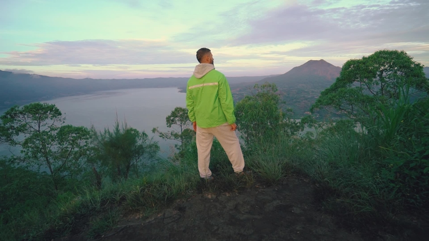Young man hiker at the top of mountain with a beautiful view at sunrise. Steadicam shot | Shutterstock HD Video #1032977096