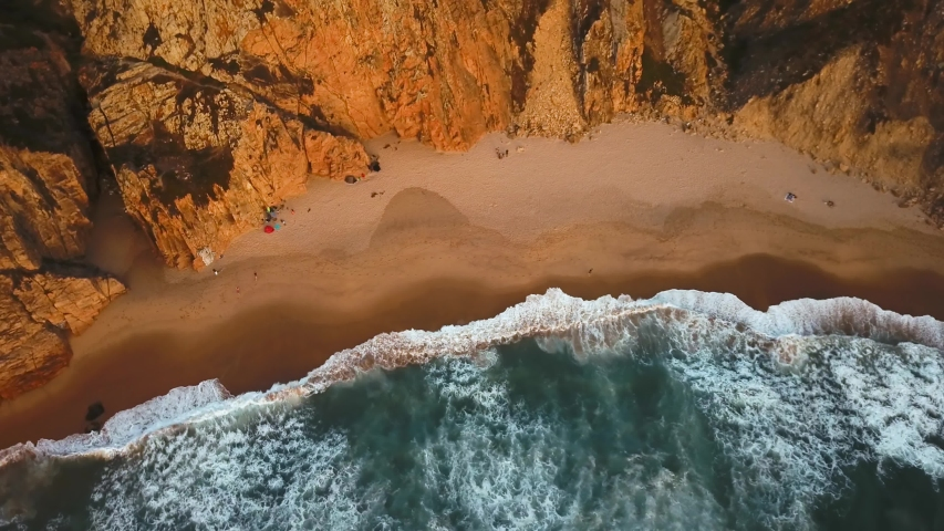 Top down view of waves breaking in the sand in Ursa Beach, Sintra, Portugal. A person running along the beach at sunset | Shutterstock HD Video #1032989666