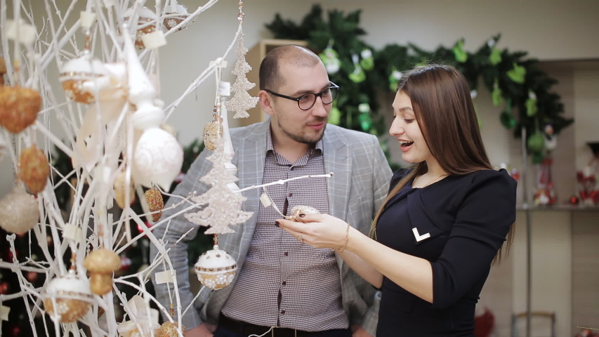 The loving couple selects the Christmas decorations in the supermarket. A woman considering Christmas balls and offers them to buy his husband. | Shutterstock HD Video #1033184006