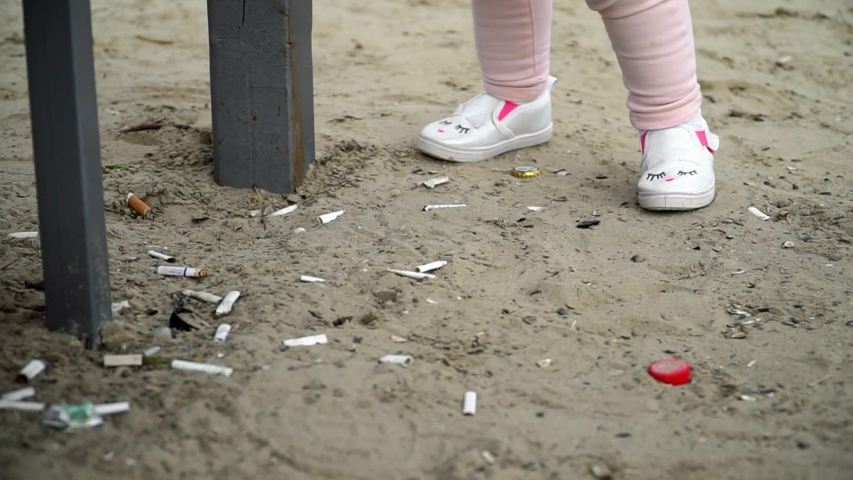 Sand on the beach with many cigarettes and baby plays. Ecology. Pollution. Addiction slow motion | Shutterstock HD Video #1033190036