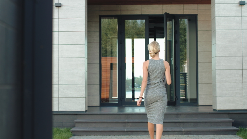 Business woman entering luxury office back view with laptop. Businesswoman going up stairs in modern building. Back view of woman walking up stairs in apartments with laptop.