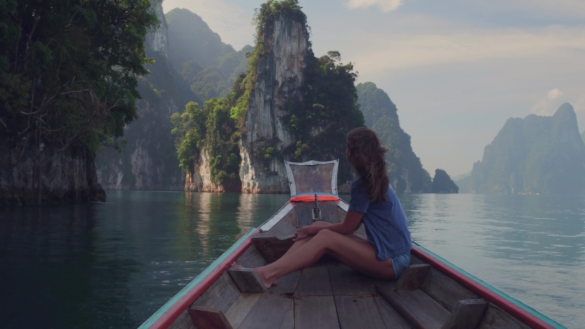 Lifestyle video of pretty travel woman sitting in wood long tail boat on tropical limestone cliffs . Explore and vacation concept. Khao Sok lake, Thailand. | Shutterstock HD Video #1033249646