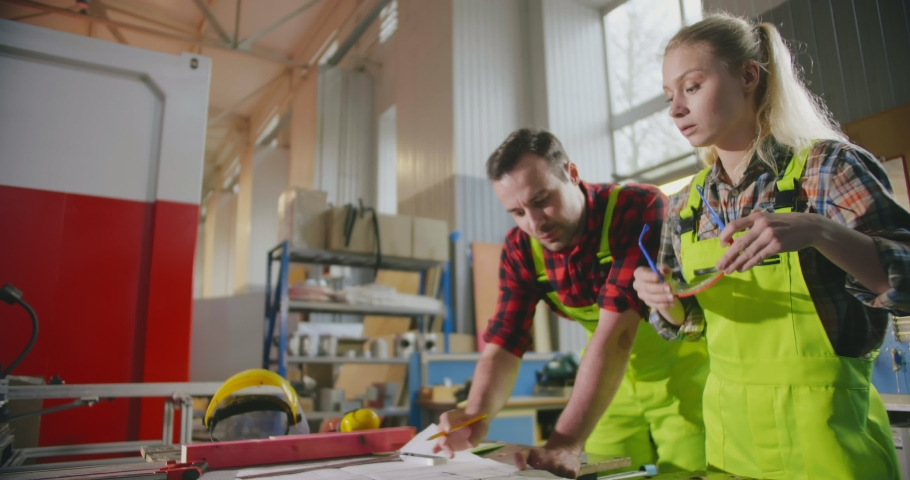 Two pensive handymasters studying blueprint and deciding their next steps | Shutterstock HD Video #1033255406