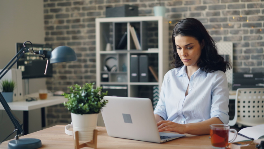 Portrait of sleepy young girl working with laptop in office then yawning and sleeping on desk lying head on computer feeling exhausted. People and lifestyle concept. | Shutterstock HD Video #1033273376