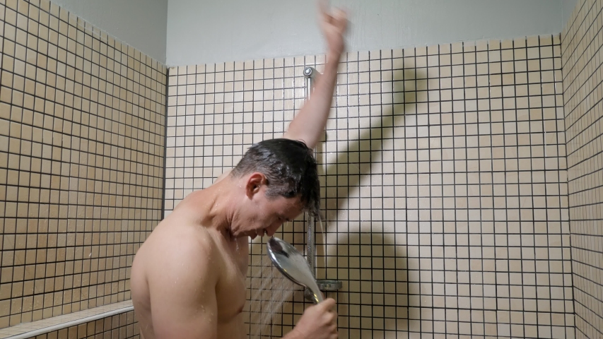 Portrait of young man singing emotionally in the shower using the shower head with flowing water instead of a microphone. Guy washes, sings and dances in the shower. | Shutterstock HD Video #1033312436