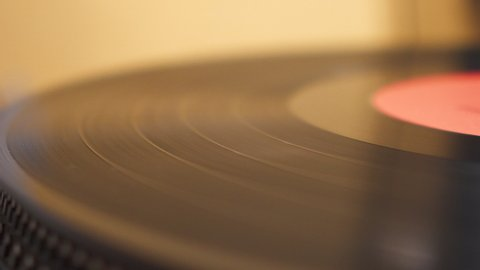 Old Vinyl Is Playing On A Silver Record Player Yellow Background Closeup View