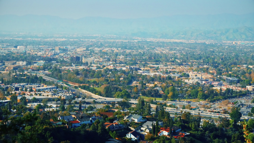 View of the city with green spaces. Green mountains in the city with a lot of beautiful trees. Freeway aerial view. Breathtaking look at busy city from the hills. Overlook in real time speed.