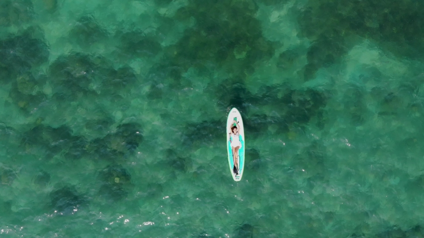 The woman on a board with an oar, SUP, swims in the sea, shooting from air | Shutterstock HD Video #1033474226