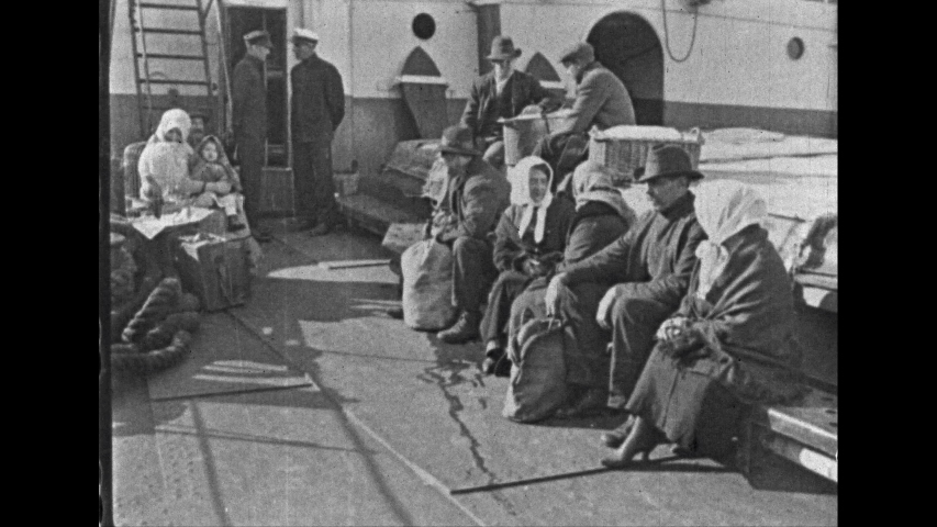 1930s: UNITED STATES: immigrants on deck of ship. People board ship. Lady puts down basket