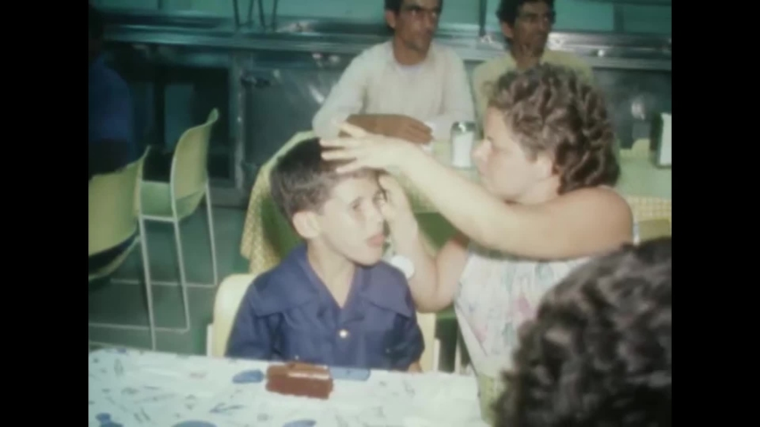 CIRCA 1980 - US Marines serve birthday cake to a young Cuban refugee and his family, who have just arrived in Key West.
