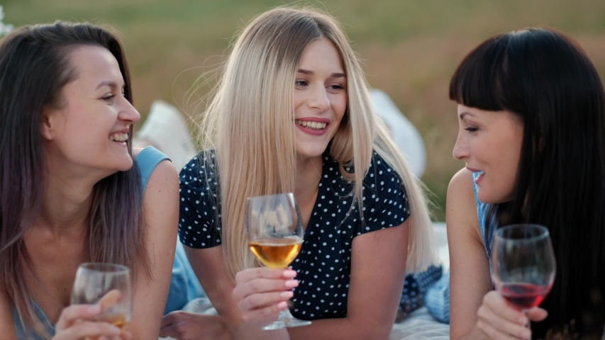 Three young women in blue dresses, and hats lie on plaid and drink wine. Outdoor picnic on grass on beach. Delicious food in picnic basket and wine. Watermelon, grapes and bouquet of daisies. | Shutterstock HD Video #1033706096