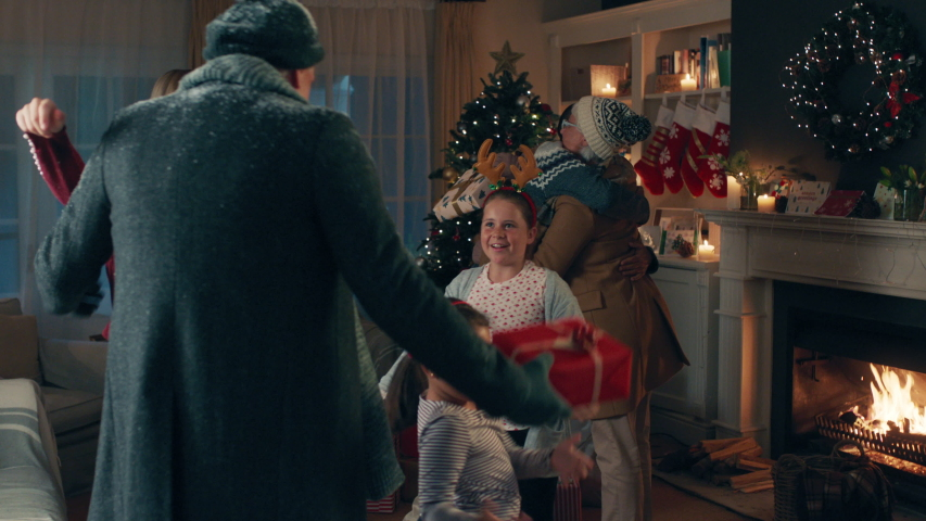 Grandparents arriving Christmas eve hugging family enjoying festive holiday celebration on winter evening at home 4k footage