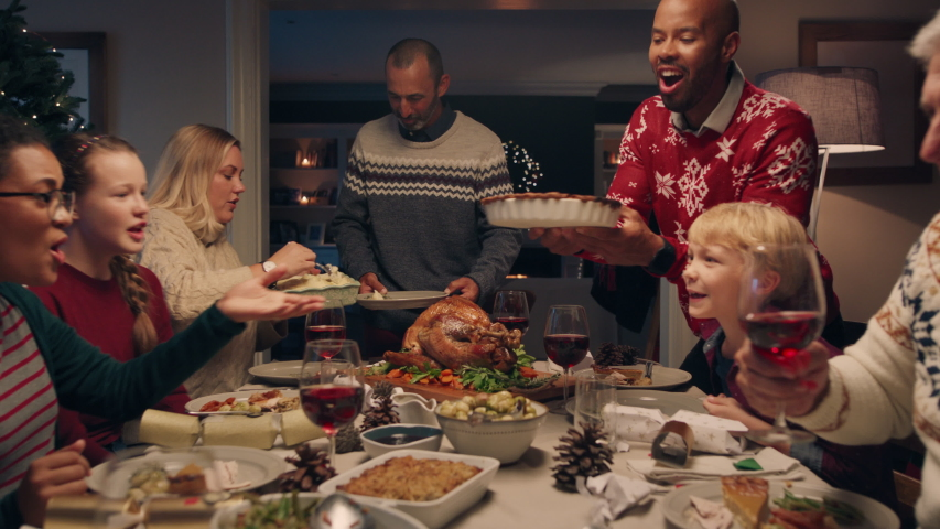 Family christmas dinner man cutting turkey serving delicious meal at festive celebration people sitting at table enjoying delicious feast celebrating holiday at home 4k footage | Shutterstock HD Video #1033939976