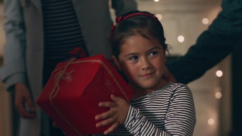 happy little girl excited to open present on christmas shaking gift box curious child enjoying festive holiday celebration with family at home 4k