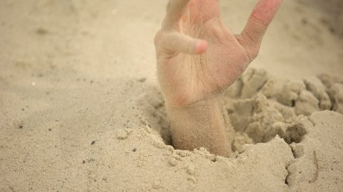 Male hand sinking in puddle of quicksand, dangerous travels in desert, closeup