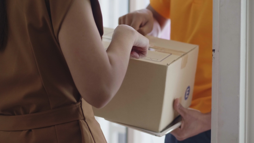 Young delivery Asian man holding a cardboard box while Asian young woman checking address on the box.   Shutterstock HD Video #1034015066