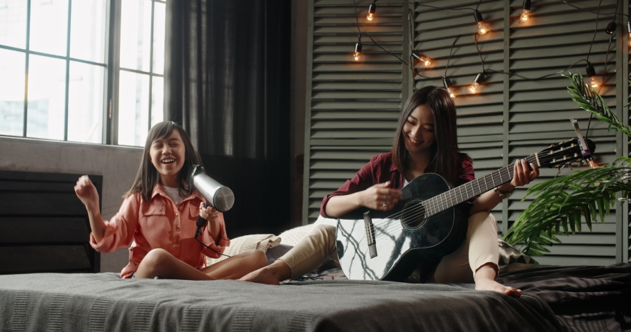 Two asian sisters sitting on bed, elder playing guitar while little kid is singing into hairdryer. Friends having fun spending time together at home - recreational pursuit, family time 4k | Shutterstock HD Video #1034041886