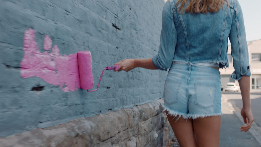 Graffiti girl artist woman painting wall with pink paint walking in city street confident rebellious female enjoying artistic expression with urban graffiti art