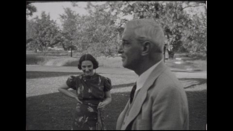 1930s: Elderly man and younger woman on front lawn, man walks off, woman smiles and points. Woman bends over grass. Baby girl in frilly dress runs down stone walkway. Woman pushes older girl in swing.