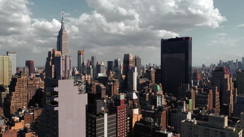 NEW YORK - JULY 24, 2019: Midtown Manhattan skyscrapers from aerial view moving over buildings toward Empire State Building in New York City NYC.