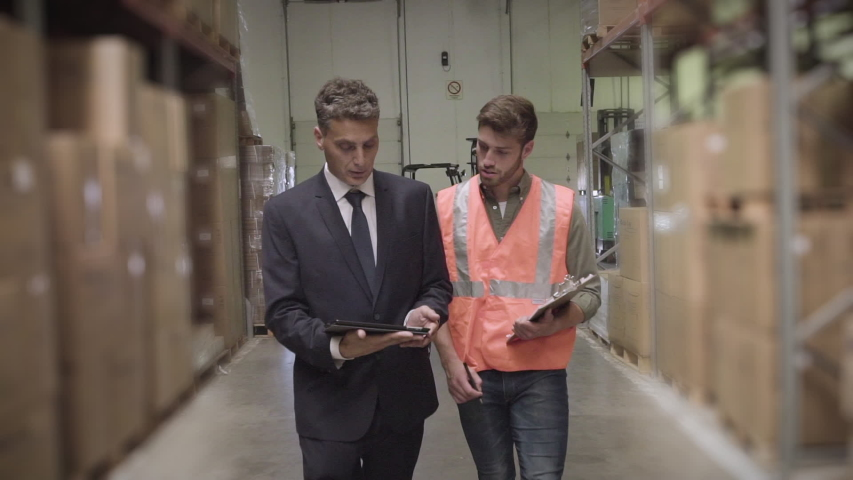 Medium shot of warehouse worker and businessman discussing with digital tablet and clipboard while maintaining records in warehouse | Shutterstock HD Video #1034131286