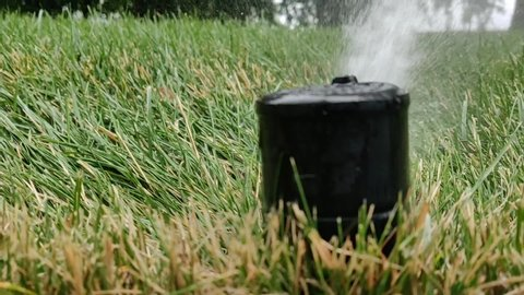 Rotating sprinkler head up close spraying away, watering a lawn
