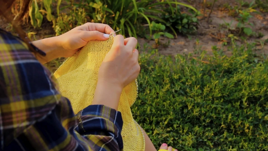 Female young hands knit a sweater with yellow threads. The process of creating facial loops of soft wool thread. crafts as a hobby. doing things you love in the garden | Shutterstock HD Video #1034193506