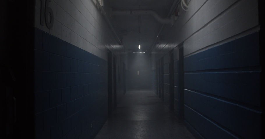 Point of view of walking down dark ominous hockey arena corridor passing through pools of light. | Shutterstock HD Video #1034197016