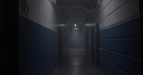 Point of view of walking down dark ominous hockey arena corridor passing through pools of light.