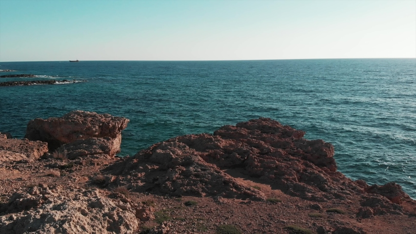 Blue ocean water and brown rocky cliffs with sun on horizon. Coral beach in cyprus. Aerial view of blue ocean water colliding with cliffs and rocks. | Shutterstock HD Video #1034205956