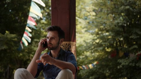 Man Talking On Mobile Phone.Handsome Bearded Man Talking By Smartphone.Young Attractive Bearded Man Sitting And Talking On Mobile Phone With Friend.Businessman Using Mobile Phone At Beautiful Place.