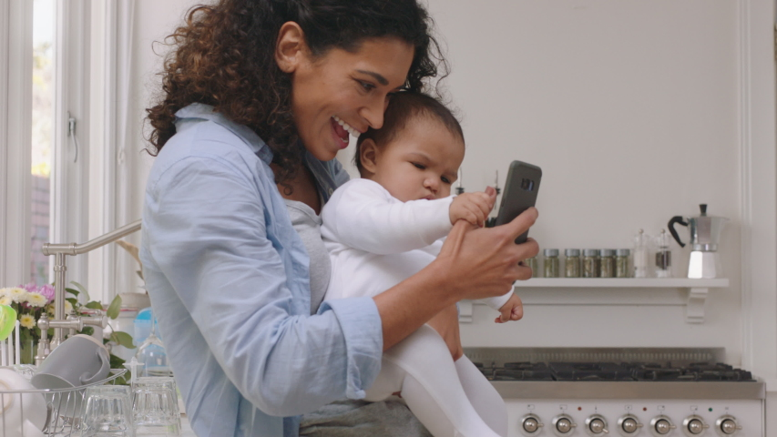 Happy mother and baby having video chat using smartphone mom holding toddler enjoying mobile technology sharing motherhood lifestyle with friend on social media | Shutterstock HD Video #1034239076