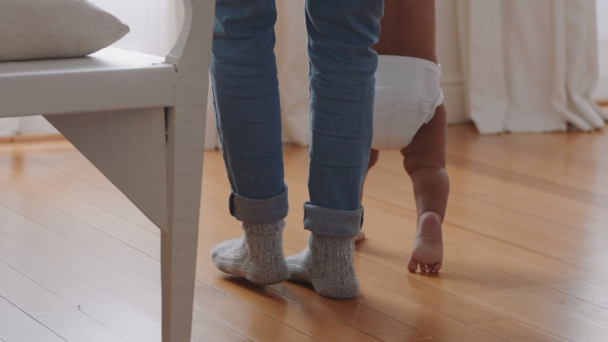 Baby learning to walk toddler taking first steps with father helping infant teaching child at home | Shutterstock HD Video #1034285756