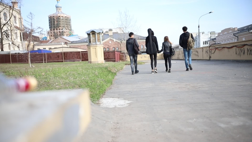 Young friends walking on the streets - bottle of alcohol drink left empty on the stand   Shutterstock HD Video #1034293496