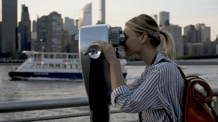 Attractive female traveller with touristic backpack using Tower Optical viewer for looking around metropolitan skyline buildings, young hipster girl with retro technology on neck exploring city #1034314076