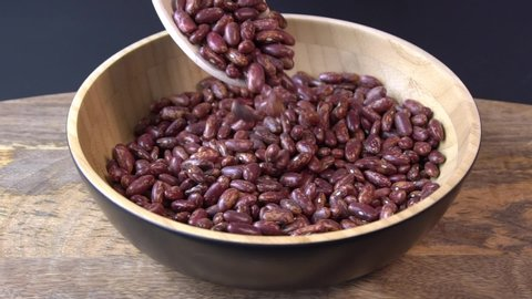 Red beans falling into a wooden bowl. Wooden background. Closeup. Food video. Uncooked beans Raw cereal falling into beautiful dishes Macro slow motion.