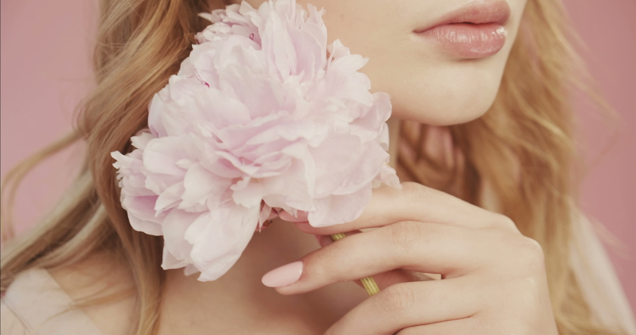 Beautiful lovely girl with nude makeup holds magnificent pink color of peony close to face. In the studio on pink background. Delicate makeup, expressive eyes. Concept for perfume and cosmetics. #1034354156