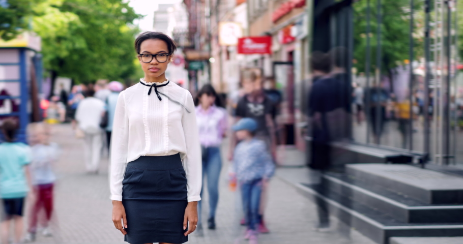 Time lapse portrait of good-looking mixed race student standing in city street on summer day looking at camera. Modern lifestyle, people and loneliness concept.
