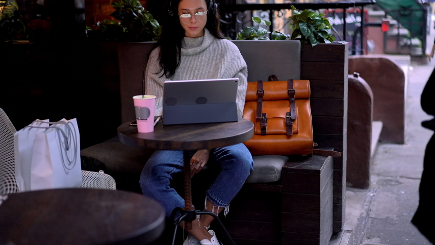 Attractive hipster girl in trendy outfit sitting at sidewalk cafeteria and using public internet connection while working remotely on media files for design project using photoshop application | Shutterstock HD Video #1034437916