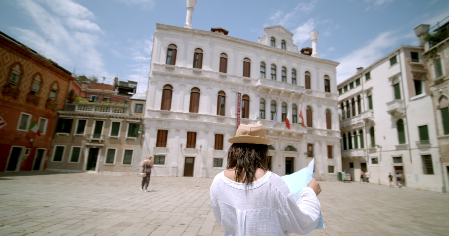 Female traveller reading street signs and map looking lost trying to find her way wearing fedora travelling abroad standing in Italian square in Venice Italy #1034464016