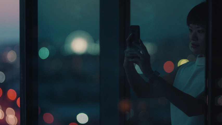 Asian business woman using smartphone taking photo of city at night enjoying beautiful view working late in office | Shutterstock HD Video #1034474786