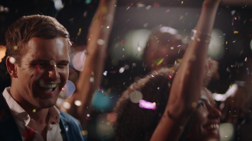 New years eve friends celebrating rooftop party dancing throwing confetti enjoying glamorous celebration wearing stylish fashion social gathering at night 4k   Shutterstock HD Video #1034504246