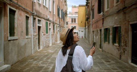 Female traveller looking up at street signs and map trying to find her way wearing fedora and using her mobile phone to find her way in Venice Italy