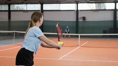 Young woman in sportswear and long hair making wide serve ball in tennis. Medium shot of female tennis player serving. Young people playing tennis in slow motion