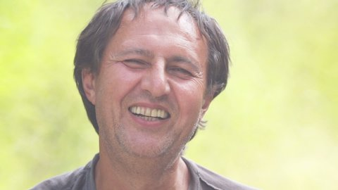 Close-up portrait of a man with a cigarette in his hand. The face of a man with a cigarette in nature.