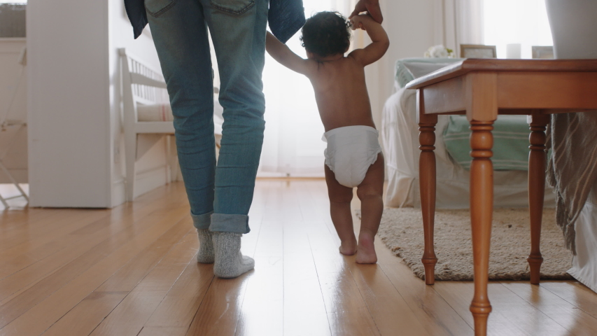Baby learning to walk toddler taking first steps with father helping infant teaching child at home | Shutterstock HD Video #1034550896