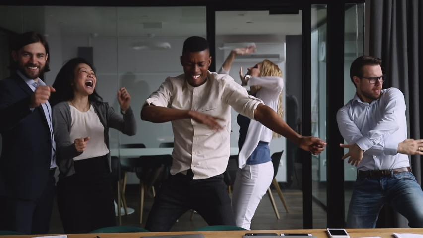 Motivated funny diverse business team people dancing celebrating success at corporate party on friday, happy friendly multiracial coworkers group having fun together enjoy victory dance in office
